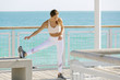 Fit latina girl stretching out on the bridge of Miami Beach