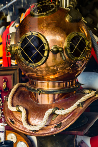 Vintage antique copper diving helmet displayed in store glass window. Historic nautical accessories traveling concept. Authentic lifestyle image.