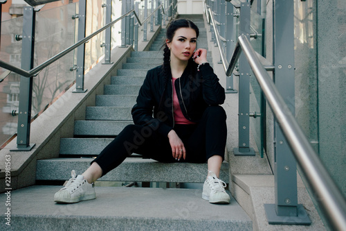 Fotografiet People, beauty, fashion, lifestyle concept -Young sexy woman with braids dressed in black pants and a black bomber jacket