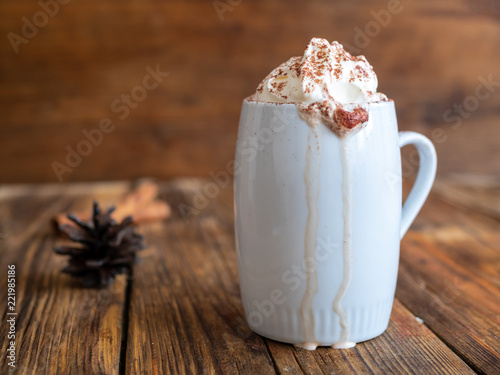 Heiße Schokolade mit Sahne und Kakaopulver auf einem braunen Holztisch, rustikal, Textfreiraum