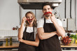 Friends loving couple chefs on the kitchen having fun with pepper as a moustache.