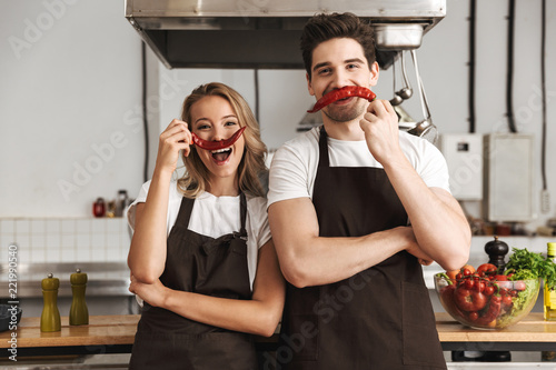Obraz Friends loving couple chefs on the kitchen having fun with pepper as a moustache. - fototapety do salonu