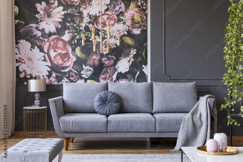 Fototapeta Blanket on grey couch in living room interior with flowers wallpaper and lamp on table. Real photo