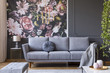 canvas print picture - Blanket on grey couch in living room interior with flowers wallpaper and lamp on table. Real photo