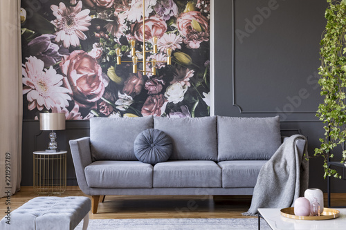 Blanket on grey couch in living room interior with flowers wallpaper and lamp on table. Real photo - fototapety na wymiar