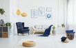 Leinwanddruck Bild - Real photo of a living room interior with blue accents, wicker pouf on the floor and poster collection