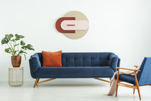 Creative Geometric Art On A White Wall Above An Elegant Blue Sofa In A Mid-century Modern Style Living Room Interior. Real Photo.