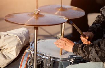 Fototapeta na wymiar Old man playing drums on street