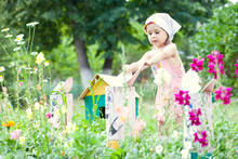 Little Girl Playing With Garden Sculptures In The Yard