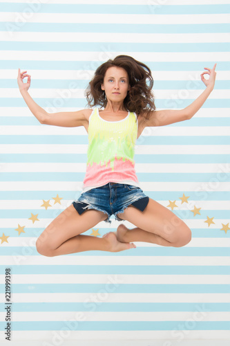 Woman fit slim lady posing as meditating while jump mid air