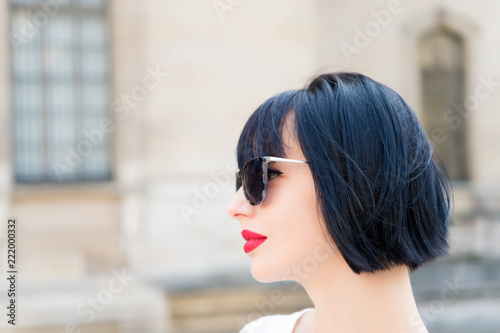 Girl fashionable lady with bob hairstyle outdoor urban architecture background Fotobehang