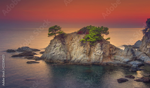 Spoed Foto op Canvas Zalm Scenery rocks and mountain on coastline in mediterranean sea at sunrise. Seascape of spanish beach at dawn. Beautiful view on sea with rocky island in morning. Landscape of sea with colorful red sky.