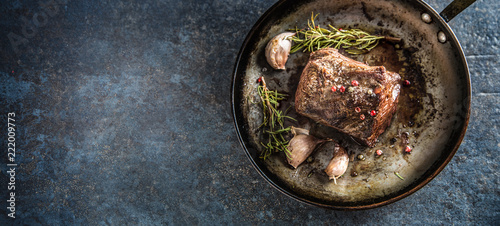 Juicy beef steak with spices and herbs in old pan