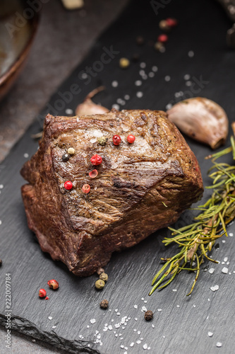 Juicy beef steak with spices and herbs on cutting board