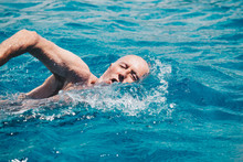 Senior Man Swimming On The Blue Ocean -health And Activity Concept.