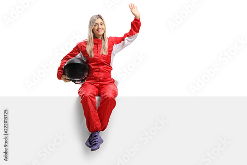 Foto op Canvas Motorsport Female racer sitting on a panel and waving