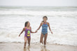 Two mixed-race sisters playing and laughing having fun on the beach on a bright tropical summer holiday