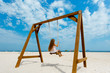 Happy girl on swing in summer day, on the seashore