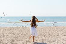 A Child In A White Dress Runs Along The Beach With Gulls