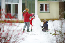 Cute Little Girls And Their Grandma Building A Snowman In The Backyard. Cute Children Playing In A Snow.