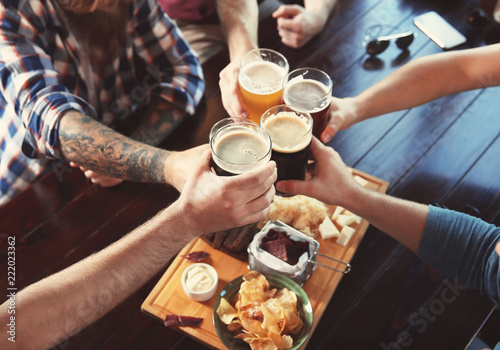 Friends clinking glasses with beer in pub Wallpaper Mural
