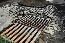Drainage Sewer Grate On The Old Road From The Broken Asphalt And Paving Blocks Wet After The Rain In One Of The Central Streets Of The City's Greater