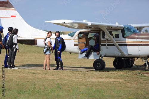 Skoczkowie ze spadochronami na plecach wsiadają do samolotu.