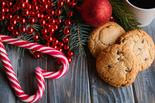 New Year Festive Decoration On Wooden Background. Chocolate Chip Cookies And Candy Canes In Heart Shape. Seasonal Foods Concept.