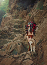 Native American Indian Woman. A Huntress With A Wolf Walks Through The Canyon, Among The Rocks. The Girl Has Ethnic Decorations. The Great, Big Dog Alaskan Malamute.