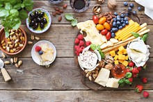 Cheese Platter With Fresh Berries And Nuts On A Rustic Wooden Table. Overhead View.