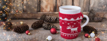 Knitted Red Cup With White Reindeer, Christmas Lights With Cones And Toys At Rustic Background, Banner