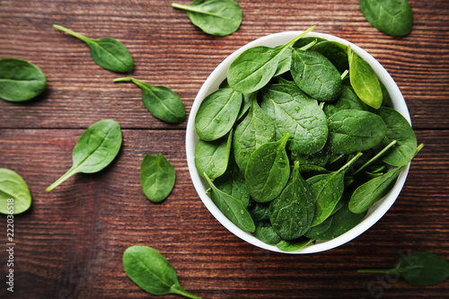 Foto op Aluminium Aromatische Spinach leafs in bowl on brown wooden table
