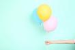 Leinwandbild Motiv Female hand holding colorful balloons on mint background