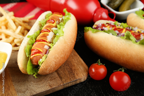 Fotografie, Obraz Hot dogs with ketchup, mustard and vegetables on wooden table