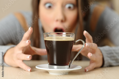 Vászonkép Amazed woman looking at coffee cup