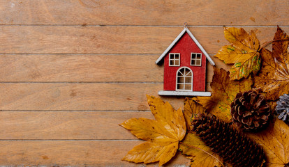 little vintage house with maple leaves on wooden table. Above view