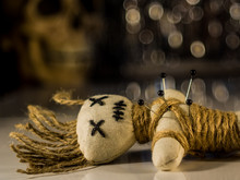 A Needle Punched Voodoo Doll Lies On A Table