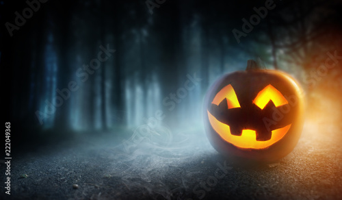A mysterious and spooky misty halloween evening background with a glowing Jack O Lantern pumpkin.