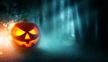 A Spooky Halloween Pumpkin Jack O Lantern Grinning On A Misty And Dark Evening.