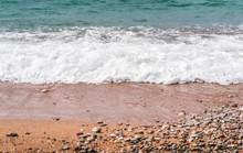 White Fluffy Waves Hitting The Beach