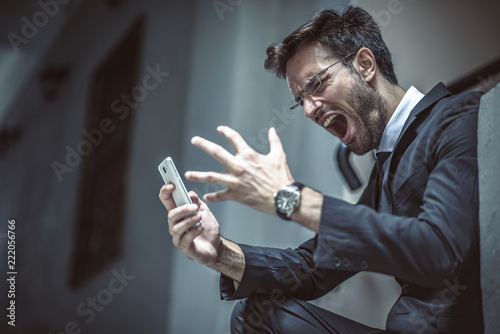 Photographie Angry, furious business man shouting at his cell phone, sitting outside a buildi