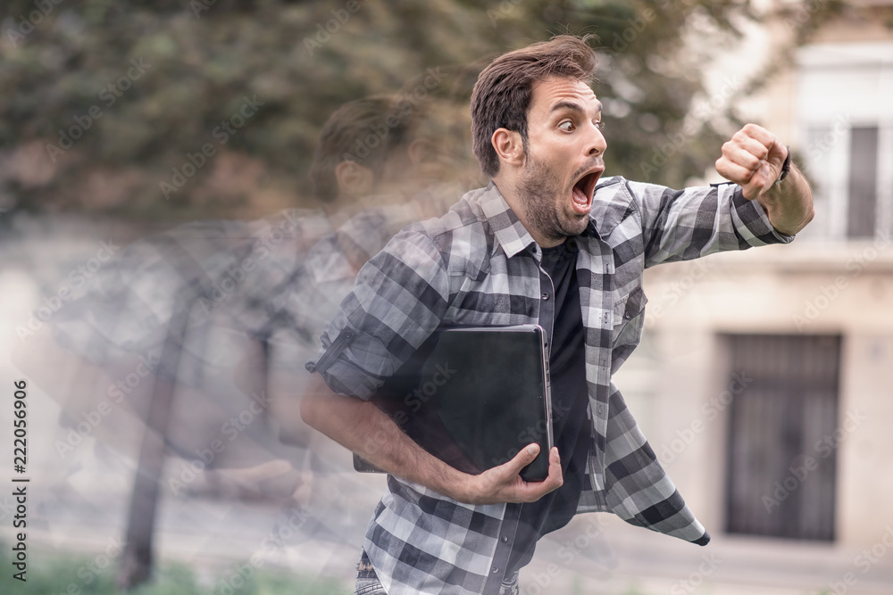 Fototapety, obrazy: Young man running late for his meeting, looks at the time on his watch, feeling stressed and sprinting to his meeting