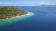 Drone footage approaching Coron Banana Island in the middle of the ocean on a bright and sunny day