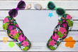 Beach flat lay with brightly patterned flip flops and sun glasses and sea shells on a white painted wooden background - room for copy