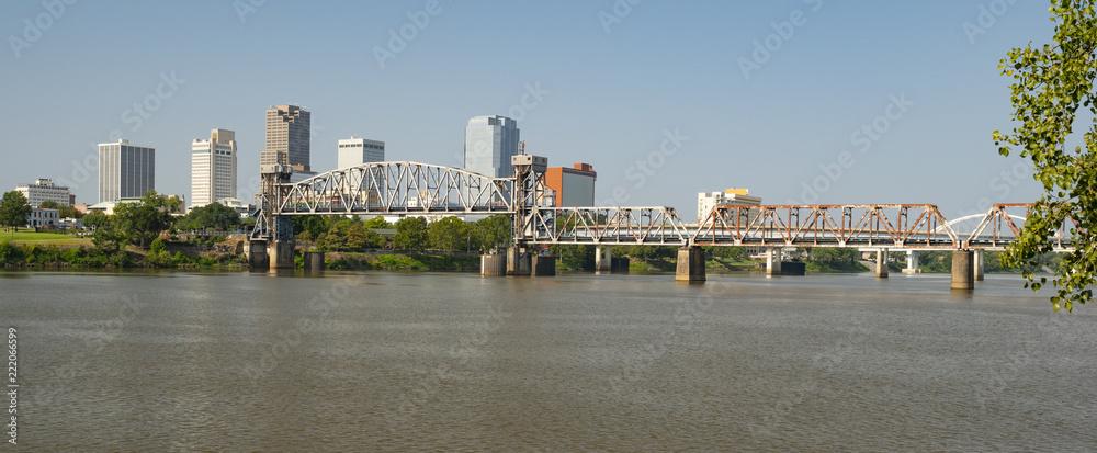 Fototapeta The Arkansas River flows by the Little Rock Waterfront under Bridges and Tresles