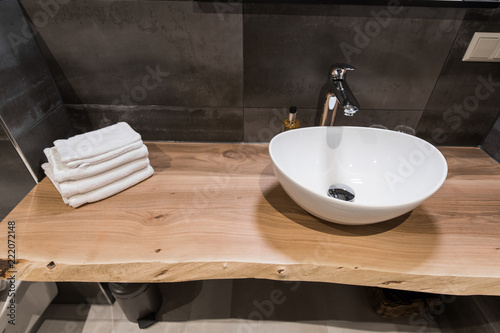 Modern interior of the bathroom. The washbasin is made of white massive shell on the table of wood. Minimalism and simplicity in a bright grey functional interior. Top view