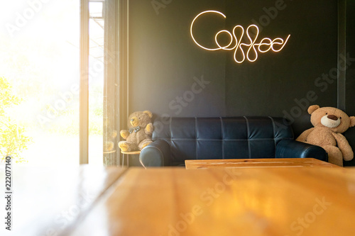 """inside modern coffee shop decorative black sofa and wooden tables and """"coffee"""" word writing with neon light on black wall background ."""