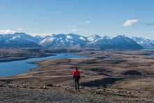 Man In Red Jacket Looking At View Of Mountains Near Lake Tekapo