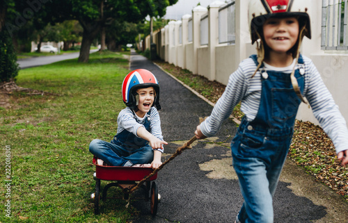 Fotografía  Identical twins playing outdoors with a trolley