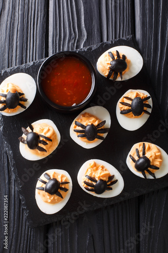 Halloween appetizer deviled eggs stuffed with mustard and decorated with olive spiders and cobweb close-up. Vertical top view